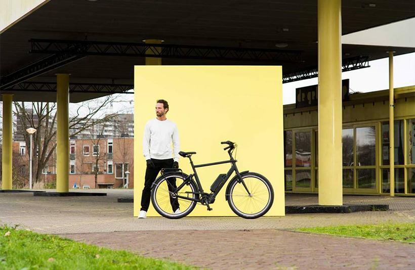 Man naast Union E-Lite fiets voor geel bord