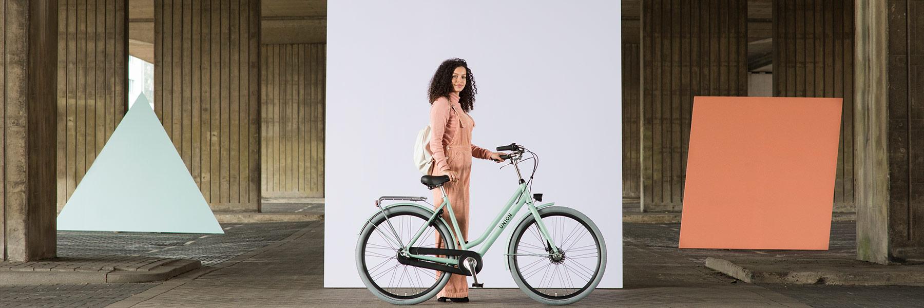 Vrouw bij groene Union fiets met handrem