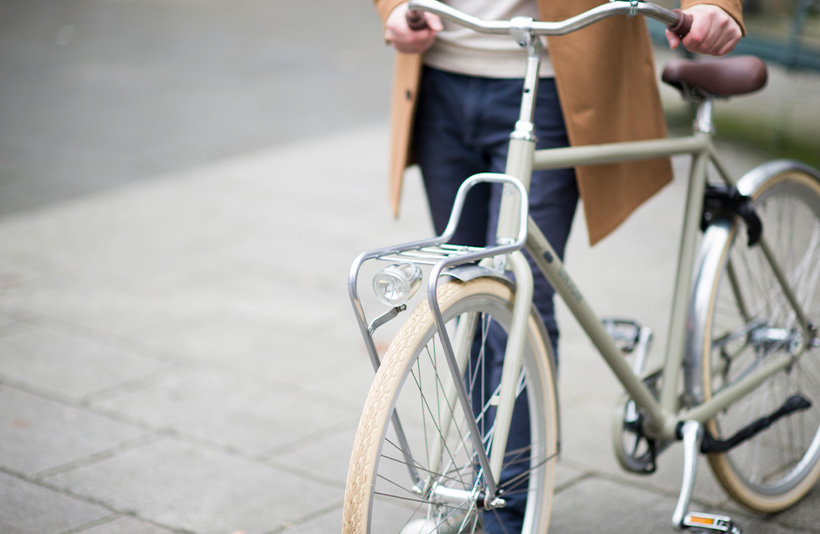 Man loopt met groene Union fiets door Leiden
